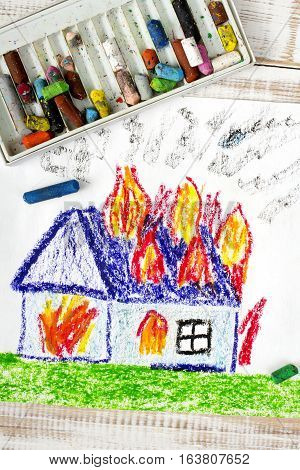colorful drawing: burning house and flames on the roof