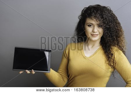 Look at this. Positive delighted female wearing yellow jersey holding black tablet in the right hand while posing at camera