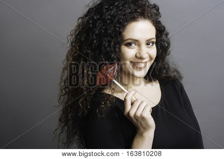 Tasty candy. Delighted brown-eyed woman holding candy in shape of lips in right hand looking straight at camera, standing over grey background