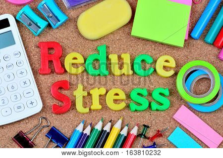 Reduce stress words on cork background closeup