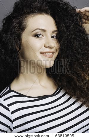 Nice day. Good looking pretty female wearing striped jumper touching her curly hair with left hand posing over grey background