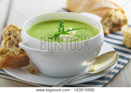 Spinach cream soup with rye bread on a table. Traditional European food for lunch. Close-up shot.