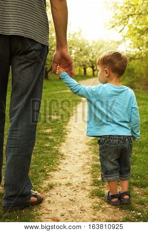 the parent holds the hand of a small child