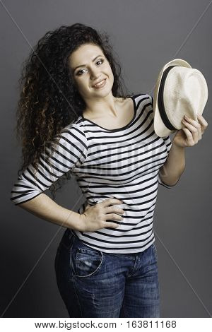 Pose like a model. Attractive smiling female wearing striped jumper and jeans holding white hat in left hand keeping her right hand on the waist while looking at camera