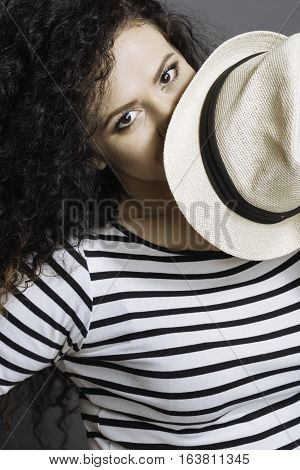 I am looking at you. Positive delighted curly brunette wearing striped jumper keeping white hat near eyes while looking at camera