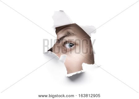 Man With Blue Eyes Looking Through White Ripped Paper Hole