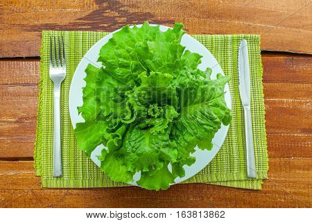 Fresh lettuce on a plate with silverware. Abstract concept of healthy vegetarian food on a table. Top view close-up.
