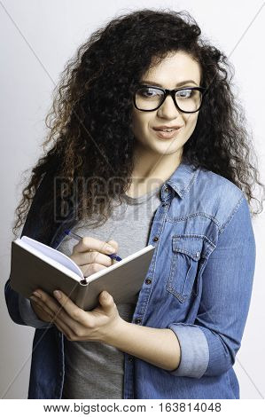 Study well. Student in glasses posing on camera at the same time writing notes and smiling