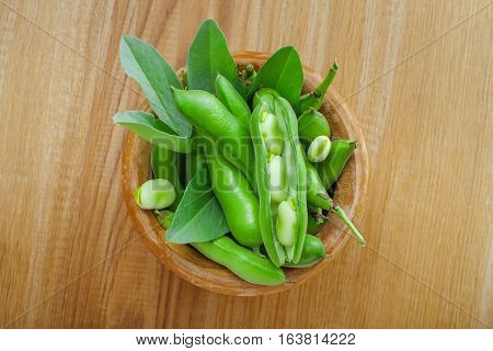 Green broad beans in a wooden bowl. Healthy raw vegetable on a table. Raw organic food.