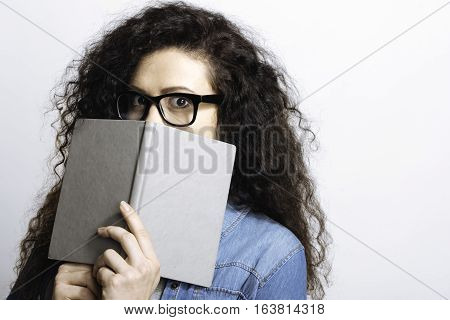 I do not know. Student perplexing covering her face with copybook, watching in surprise standing over white background