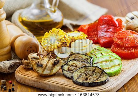 Set of grilled vegetables meal: tomato corn eggplant mushroom bell pepper marrow and onion. Healthy organic food on a table.