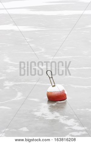Red snowy marine buoys in frozen sea water at winter