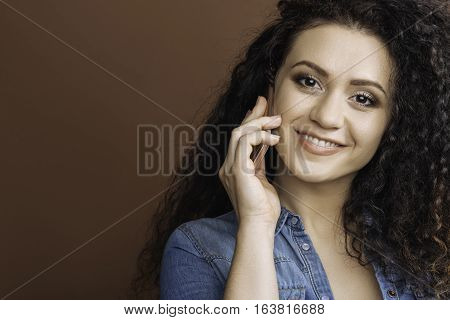 Expectant call. Pretty smiling woman with curly hair looking straight at camera using phone while speaking, isolated on brown background