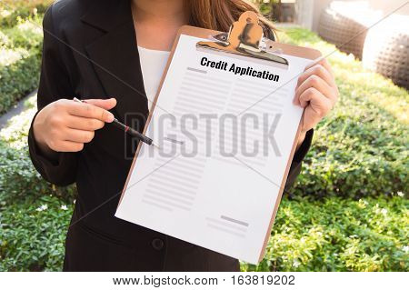 Women in suit showing approved credit application and pointing with a pencil with sunlight