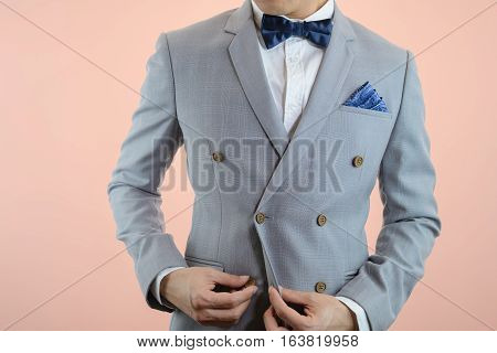 Man in grey suit plaid texture blue bowtie and pocket square close up white background