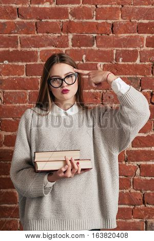 Tired student with books shows shooting gesture. Exhausted girl need rest from intensive tutorial. Education, tiredness concept