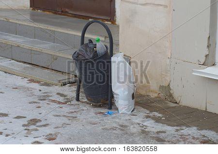 Overload waste basket on the city street.