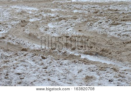 Tracing ruts on dirty snow. Abstract background.