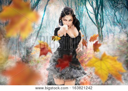 Magician witch power girl. Superpowers dark sorceress woman. Fall foliage forest. A beautiful sorceress queen with black suit unleashes her power. Environment fantasy darkness spooky forest. Fog and smoke.