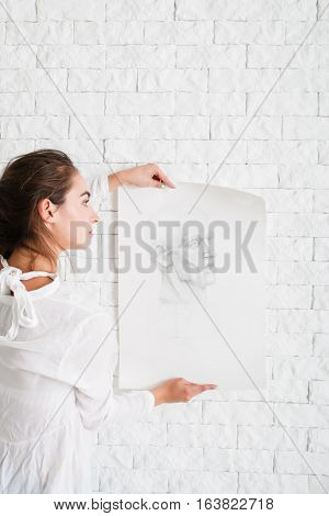 Artist hanging her pencil portrait on wall. Close-up of attractive woman decorating white brick side in her workshop with sketch. Art, creativity, hobby, talent, drawing, relax concept