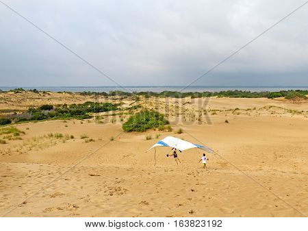NAGS HEAD NORTH CAROLINA - JULY 29 2013: Student prepares for landing with an instructor from the Kitty Hawk Kites Hang Gliding School on the sand dunes of Jockeys Ridge State Park on the Outer Banks