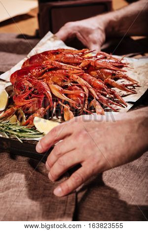Dish it up. Close up of mans hands holding a wooden tray with crayfishes while serving it in a restaurant.