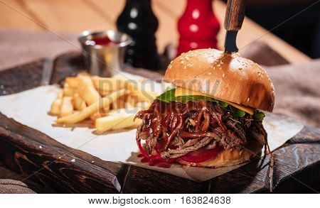 Perfect menu. Close up of big burger being served with French fries and sauce in restaurant while standing on a table.