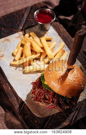 Taste and look. Top view of big burger standing on a wooden tray and being served with French fries and sauce in restaurant.
