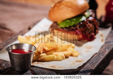 Like that dish. Close up of sauce being served to burger and French fries while standing on a table in restaurant.