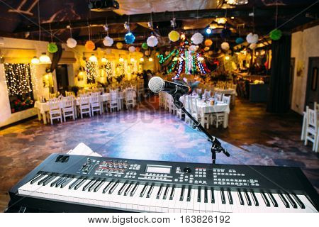 synthesizer and microphone on a stage in a large hall