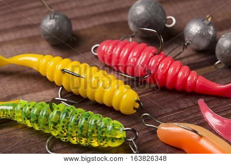 Colourful rubber fishing baitswith plummets close-up on wooden table. Selective focus.