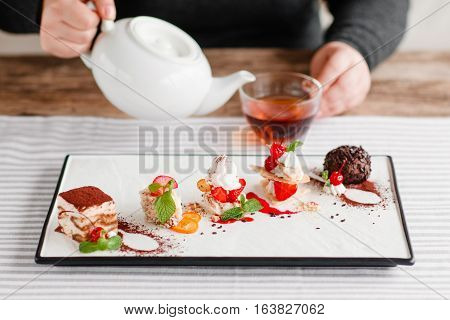 Drinking afternoon tea with sweet desserts. Plate with different pieces of cakes on table, man pouring tea into cup on blurred background. Pastry, bakery, confectionery concept