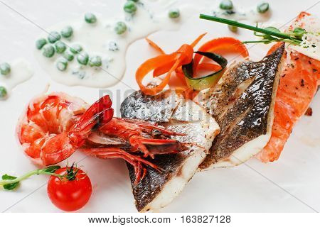 Grilled seafood mix on white background closeup. Appetizing roasted red and white fish fillet with shrimp and pea sauce. Mediterranean cuisine, gourmet food, delicatessen concept