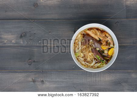 noodle soup in bowl on a wooden table top view Thai local food