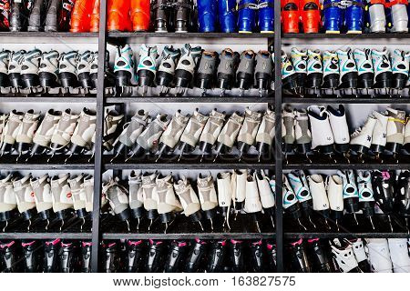 Ski boots and ice skates on shelf in winter ski rent or shop