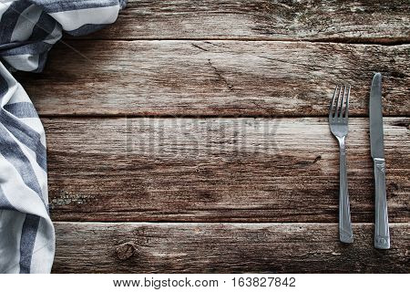 Cutlery and napkin frame on old wooden table. Knife and fork with kitchen towel on rustic table, void, free space for meal advertisement or restaurant menu