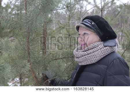Mature woman in the woods. Intently looks into the distance