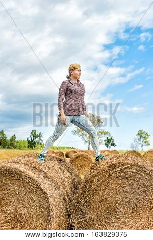 Young woman balancing on hay roll bales