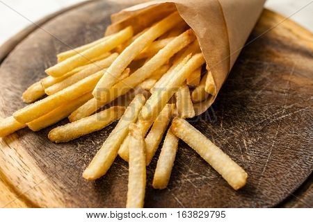 Portion of french fries on catering platter. Closeup of paper pack with traditional american fried potato. Junk fast food, restaurant menu, snack concept