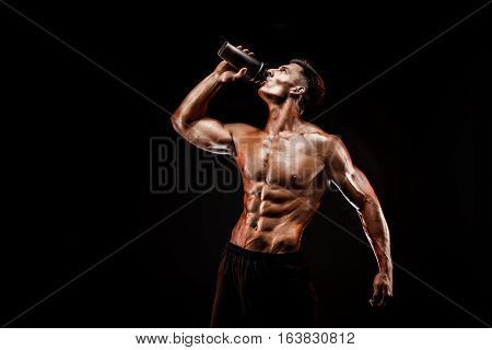 Muscular man with protein drink in shaker over dark background