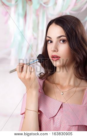Beautiful woman painting her face with brush. Attractive brunette in pink looking at camera, while she powdering her face with rouge. Makeup, beauty, fashion concept