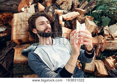 Man using smartphone on pile of wood. Lumberman networking, chatting, reading news on mobile phone while having rest on bunch of firewood. Communication, modern technologies concept