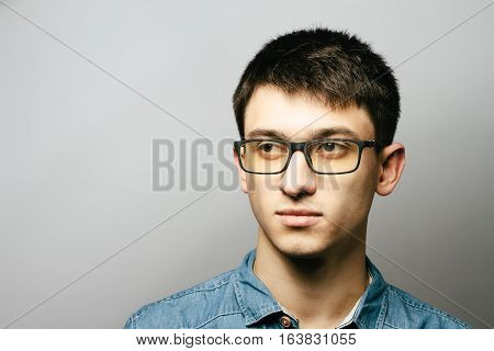 Close Up Smiling Young Businessman Wearing Eyeglasses, Looking At The Camera Against Gray Wall Backg