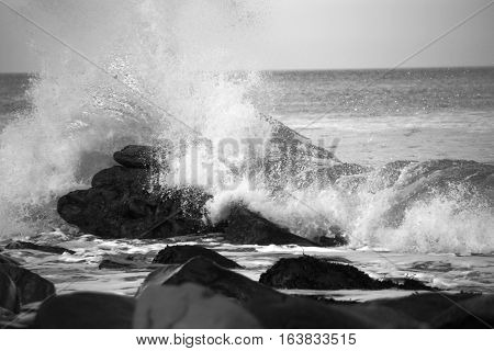 waves crashing over rocks on the sea shore in black and white