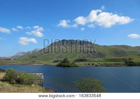cadair idris behind a mountain lake bathed in sunshine in snowdonia national park