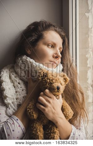 Sick girl sitting with a bear in the hands of the window. Young girl is sick and stays at home by a window with a scarf and teddy bear.