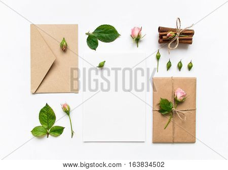 Letter envelope and a present in eco paper on white background. Wedding invitation cards or love letter with pink roses. Valentine's day or other holiday concept top view flat lay overhead view