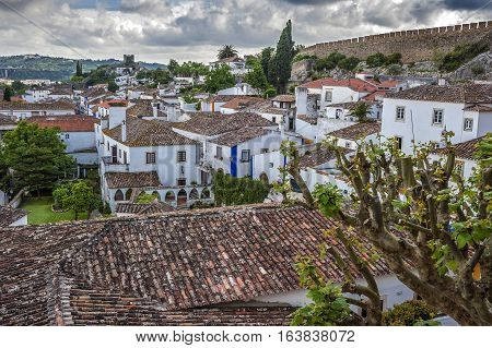 Portugal Obidos - urban village and the castle of the same name with the fortress. Flowers fruit trees white villas paved paths quiet streets .