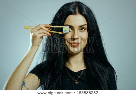 Pretty gothic girl posing with chopsticks posing over white background