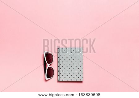 Silvery dotted diary, glasses on pink background. flat lay, top view. Feminine workspace.
